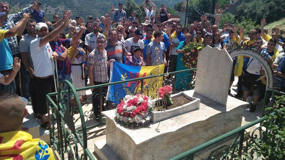Recueillement sur la tombe d'Ameziane Mehenni : drapeaux kabyles, gerbes de fleurs et youyous